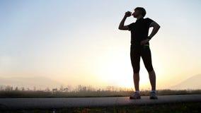 O corredor de maratona bebe a água na paisagem larga da montanha do ângulo