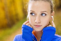 O corredor desportivo da mulher escuta a música na natureza Foto de Stock Royalty Free