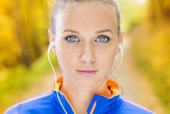 O corredor desportivo da mulher escuta a música na natureza Fotos de Stock Royalty Free