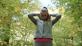 O corredor em um parque do outono joga uma capa sobre sua cabeça e começa-a correr video estoque
