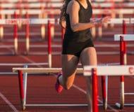 O corredor fêmea bate um obstáculo durante a raça imagens de stock