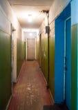 O corredor interior dilapidou porta do apartamento em um dormitório velho Imagens de Stock Royalty Free