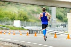 O corredor masculino na compressão golpeia o corredor na estrada com segurança dos cones do tráfego Foto de Stock