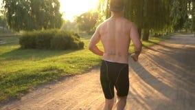 O corredor masculino novo corre ao longo da estrada com o o seu de volta à câmera vídeos de arquivo