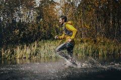 O corredor masculino que cruza um rio da montanha, em torno dele água espirra Fotos de Stock Royalty Free