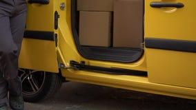 O correio põe caixas dentro da camionete amarela vídeos de arquivo