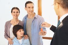 O corretor de imóveis está apresentando chaves à família no apartamento novo com caixas de cartão foto de stock
