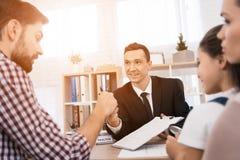 O corretor de imóveis explica ao homem adulto que dados é necessário fazer no original para a compra da casa imagens de stock royalty free