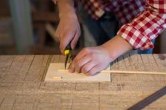 O cortador do marceneiro corta uma vara de madeira feita dos brinquedos de madeira, conceito de Fotos de Stock Royalty Free