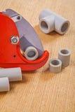 O cortador e o polipropileno de tubulação cutted as tubulações em placas de madeira Imagem de Stock