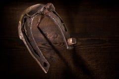 O cortador em ferradura horned velho pendurou em uma cegonha velha em um fundo de madeira fotos de stock
