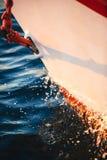 O corte da curva do veleiro através da água, dianteiro, a vela e a corda náutica yacht o detalhe Vela, fundo marinho foto de stock