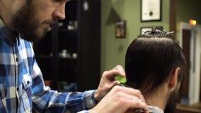 O corte do cabelo do ` s dos homens scissors em uma barbearia Feche acima da vista video estoque
