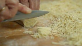O corte dos macarronetes rola na placa de corte pelas mãos perto acima filme