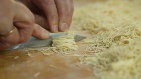 O corte dos macarronetes rola na placa de corte pelas mãos perto acima vídeos de arquivo