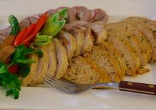 O corte dos rolos dos tipos diferentes de carne, decorou com ervas e o rabanete frescos fotografia de stock