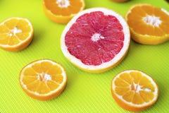 O corte fresco frutifica citrinos em um fundo verde Fotos de Stock Royalty Free