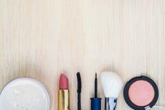 O cosmético das mulheres e compõe no fundo de madeira Imagens de Stock Royalty Free