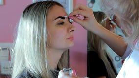 O Cosmetologist corrige um contorno das sobrancelhas ao pintar filme
