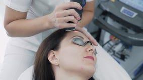 O cosmetologist do close-up faz o procedimento de remoção à cara da jovem mulher na clínica, movimento lento do laser do cabelo filme