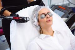 O cosmetologist do close-up faz um tratamento à cara da jovem mulher, procedimentos do laser do epilation da remoção do cabelo em fotografia de stock