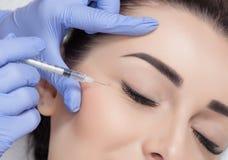 O cosmetologist do doutor faz o procedimento facial rejuvenescendo das injeções para apertar e alisar enrugamentos na cara fotografia de stock