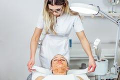 O Cosmetologist está fazendo a máscara da casca da cara, tratamento da beleza dos termas para a moça Modelo, close-up Clínica de  Foto de Stock