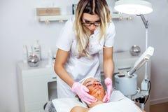 O Cosmetologist está fazendo a máscara da casca da cara, tratamento da beleza dos termas para a moça Modelo, close-up Clínica de  Imagem de Stock Royalty Free