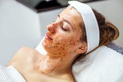O Cosmetologist está fazendo a máscara da casca da cara, tratamento da beleza dos termas para a moça Modelo, close-up Clínica de  Imagem de Stock