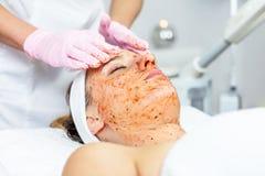 O Cosmetologist está fazendo a máscara da casca da cara, tratamento da beleza dos termas para a moça Modelo, close-up Clínica de  Fotos de Stock