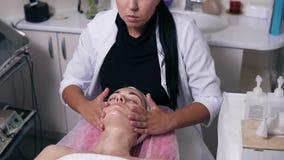 O cosmetologist fêmea concentrado está fazendo a massagem de cara no salão de beleza dos termas A jovem mulher com seus olhos fec filme