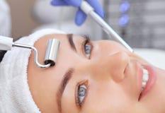 O cosmetologist faz ao instrumento um procedimento da terapia de um bonito, jovem mulher de Microcurrent em um salão de beleza imagens de stock royalty free