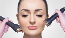 O cosmetologist faz ao procedimento uma limpeza ultrassônica da pele facial de um bonito, jovem mulher em um salão de beleza foto de stock royalty free