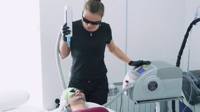O Cosmetologist faz a cara de carbono que descasca o procedimento à jovem mulher em vidros protetores, movimento lento vídeos de arquivo