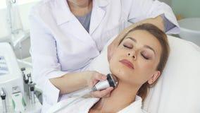 O Cosmetologist faz a massagem facial com equipamento especial video estoque