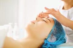 O Cosmetologist faz a massagem facial a uma jovem mulher foto de stock royalty free