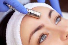 O cosmetologist faz o procedimento Microdermabrasion da pele facial de um bonito, jovem mulher em um salão de beleza O cosme foto de stock royalty free