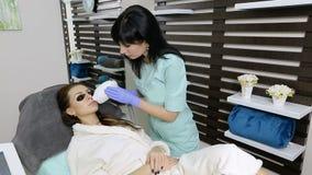 O Cosmetologist faz a remoção do cabelo do laser na cara do paciente Procedimento de Epilation video estoque
