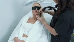 O Cosmetologist faz a remoção do cabelo do laser da cara da mulher no salão de beleza, steadicam disparou, fim acima vídeos de arquivo