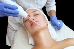 O cosmetologist faz a terapia de Microcurrent do procedimento da pele facial de um bonito, jovem mulher em um salão de beleza imagens de stock royalty free
