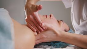 O Cosmetologist faz uma massagem especial do pescoço a seu cliente para o levantamento da pele video estoque