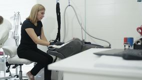 O Cosmetologist gerencie no equipamento médico especial antes do procedimento no centro da beleza, lento-movimento filme
