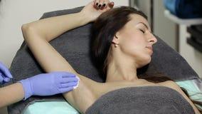 O Cosmetologist limpa as axila pacientes do ` s com a esponja do algodão antes do procedimento disinfection filme