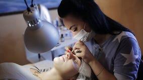 O cosmetologist mestre trabalha com um nebulizer após o procedimento, extensões da pestana Procedimento da extensão das pestanas  filme