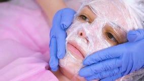 O Cosmetologist põe um filme plástico sobre a máscara hidratando sobre a cara da mulher video estoque