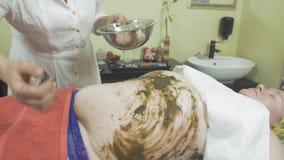 O Cosmetologist pôs a mistura da alga sobre o estômago gordo da mulher, mão esquerda no bar filme