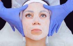O cosmetologist para o procedimento de limpar e de hidratar a pele, aplicando uma máscara da folha à cara de uma jovem mulher imagem de stock royalty free