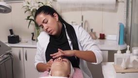 O cosmetologist profissional está fazendo a massagem de cara no salão de beleza dos termas A jovem mulher está falando a seu cosm video estoque
