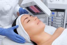 O cosmetologist usa a lâmpada de madeira para diagnóstico detalhado da condição de pele fotos de stock