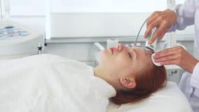 O Cosmetologist usa a máquina ultrassônica para a cara do ` s do cliente foto de stock royalty free